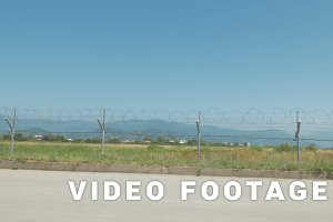 Walking along the barbed wire fence of the airport. Batumi, Geoargia