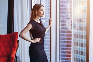 Well-off attractive woman thinking standing at the window admiring cityscape in her penthouse apartment
