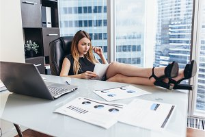 Young businesswoman reading the documents sitting with her legs on desk in office