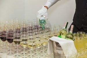 Waiter pours wine