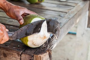 Man chopping coconut by big knife