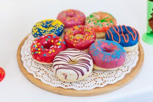 Picture of assorted donuts in a box with chocolate frosted, pink glazed and sprinkles donuts