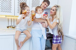 Funny family of four on the background of bright kitchen beautiful have fun fooling around eating donuts. The concept of family happiness. The full family.