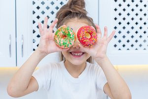 Close-up of pretty girl with double buns looking through the two sprinkled donuts on the background of bright kitchen