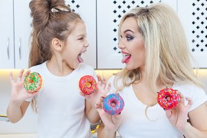 Funny family on the background of bright kitchen. Mother and her daughter girl are having fun with colorful donuts. Dieting concept and junk food. Yellow, pink and red colors