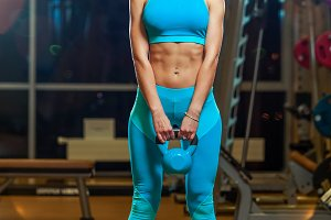 Attractive female athlete performing a kettlebell in gym.