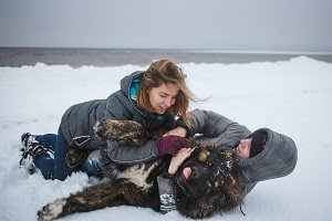 Girl and man is playing with dog in snow, Happy holidays, love moments and rest in nature in winter