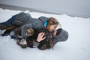 Girl and man kissing and playing with dog in snow, Happy holidays, love moments and rest in nature in winter