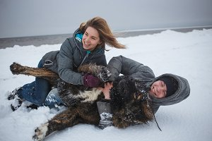Cheerful couple lying on snow with dog. Winter Holidays, love moments, happy time