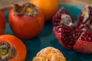 Tangerine, persimmon and pomegranate in a ceramic plate