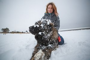 Master and her obedient Caucasian Shepherd) dog playing in winter forest