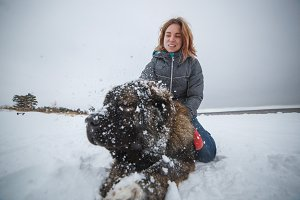 Happy girl and dog in winter snow. Wonderful holidays in nature