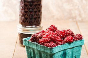 Fresh tayberries with jars of jam