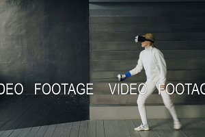 Concentrated fencer woman using virtual reality headset for play fencing training simulator game indoors