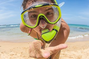 Woman on beach vacation holidays with snorkel lying in sand with snorkeling mask and fins smiling happy enjoying the sun on sunny summer day. Multi ethnic Asian Chinese / Caucasian woman model.