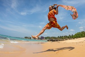 Beautiful man running and jumping in the beach with a colored tisue