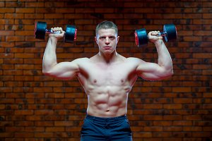 Muscular man working doing exercises with dumbbells, strong male naked torso abs on the background of red brick wall
