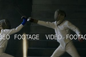 Slowmotion of Two fencers man and woman have fencing match indoors