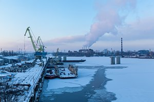 In the port of the river is covered with ice.The ships are berthed.Them loaded with goods.