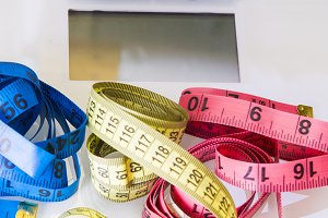 digital balance with colored measuring tape, concept of diet and slimming