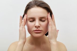 Portrait of young female model with closed eyes making herself facial massage