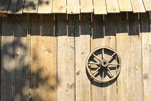 Wooden wheel on the wall of the barn