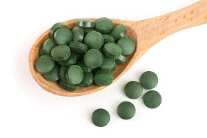 heap of Spirulina tablets algae nutritional supplement in wooden spoon isolated on white background close up top view