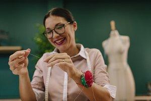 Dressmaker threading the needle