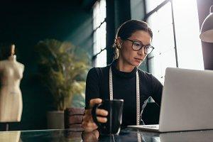 Female dress designer using laptop
