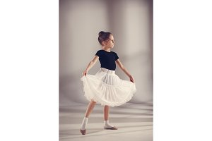 The little balerina dancer on gray background