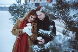 PIne branches covered snow with young couple on background
