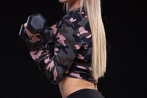 athletic young woman doing a fitness workout with dumbbells on black studio background in clothes of military colors