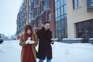 Photo of happy man and pretty woman walking outdoor along cold winter street