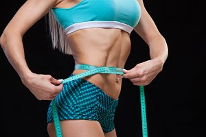 Athletic slim woman measuring her waist by measure tape after a diet over black background