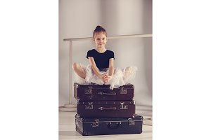 The little girl as balerina dancer sitting at studio