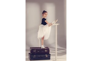 The little girl as balerina dancer standing at studio