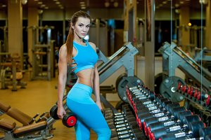 photo of sexy young woman resting in the gym and leaning on row of dumbbells