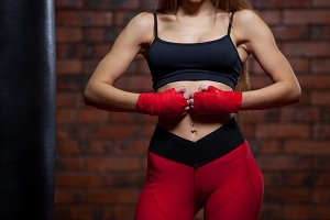 Young women boxing, the boxing bag. red bandage on hands