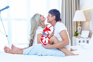 Young Happy Couple Lying In Bed, Hispanic Man Give Woman Surprise Present Envelope With Ribbon, Anniversary Celebration, Lovers In Bedroom