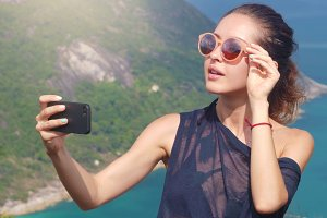 Beautiful girl traveler is taking a selfie with sea view at a height