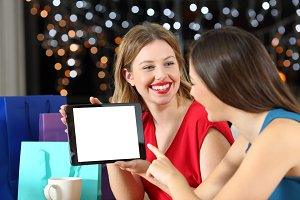 Two fashion shoppers showing tablet