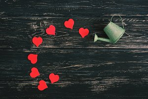 Red hearts pour out of watering can