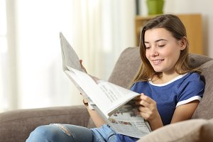 Happy teen reading a newspaper