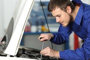 Young mechanic repairing a car