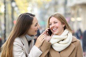 Two happy friends talking on phone