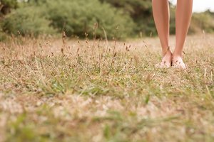 Female legs walking on the grass