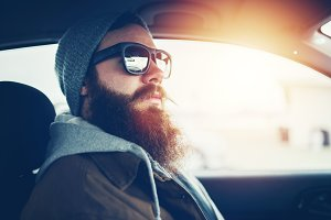 hipster with awesome beard in car