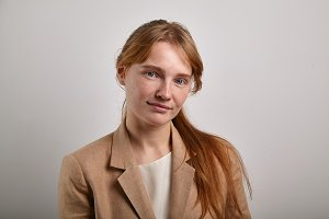Horizontal headshot of young redheaded girl with freckles wearing beige jacket