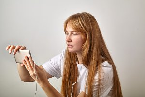 Horizontal image of young red-headed girl with freckles holding her phone