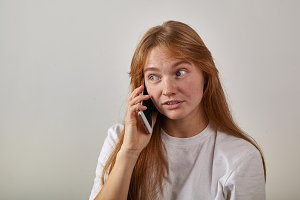 Portrait of young red-headed girl with freckles holding her phone next to her ear and talking